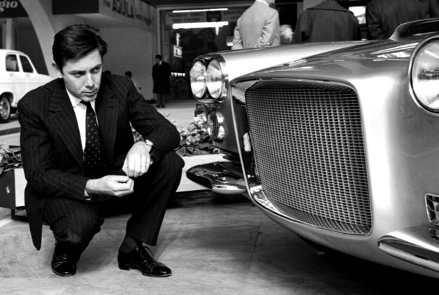 Sergio Pininfarina kneels down to inspect a car - 1959