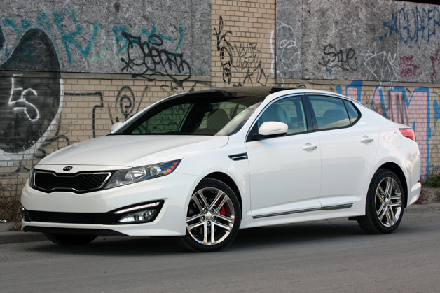 2013 Kia Optima SX Limited - white - front three-quarter view against tagged wall
