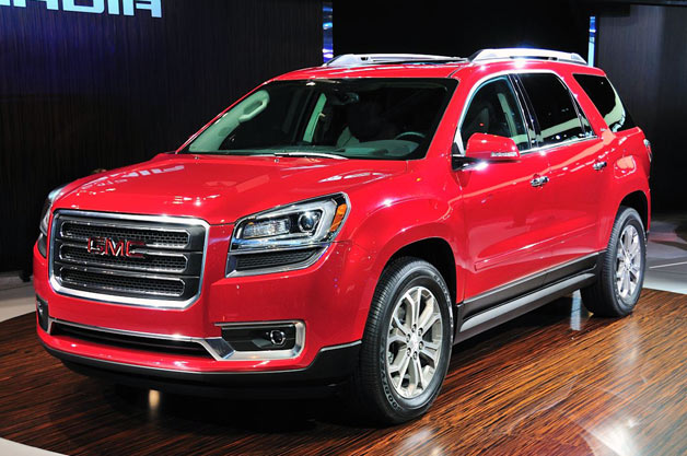 2013 GMC Acadia on Chicago Auto Show stand - front three-quarter view, red