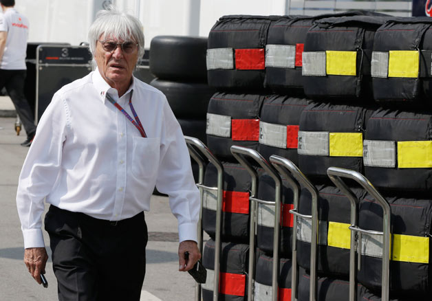 F1 boss Bernie Ecclestone walking in front of tires