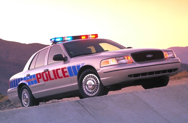 Ford Crown Victoria Police Interceptor with lights on - front three-quarter view