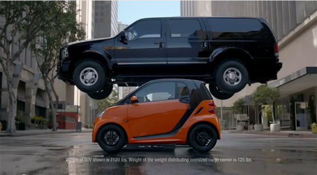 Smart ForTwo with SUV on roof - advertisement screencap