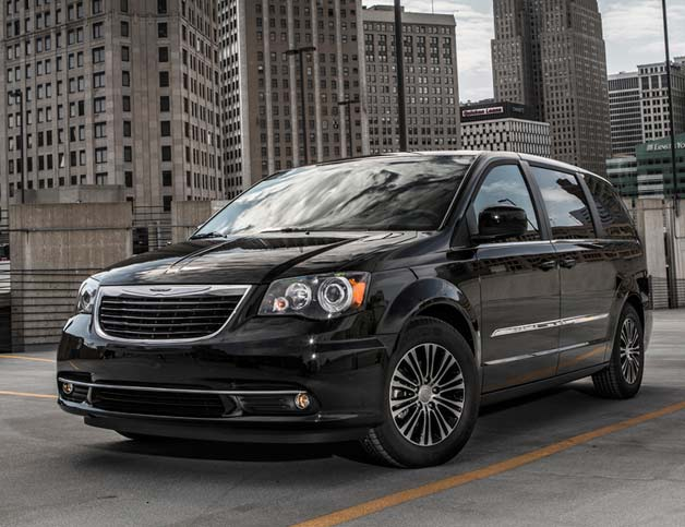 2013 Chrysler Town and Country S - front three-quarter with city backdrop.