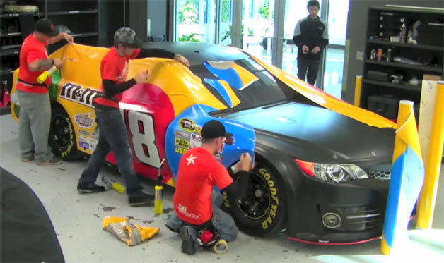 Joe Gibbs Racing wrapping Kyle Busch's 2013 Toyota Camry racecar in M&M livery - video screencap