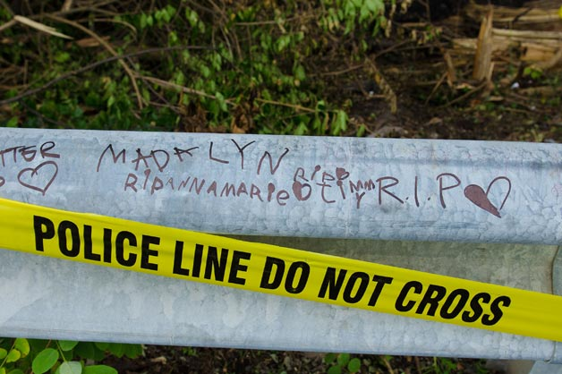 Guard rail with RIP messages and police line tape