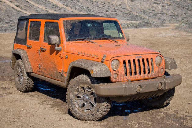 2013 Jeep Wrangler Unlimited Rubicon 4x4 - orange - front three-quarter view, muddy