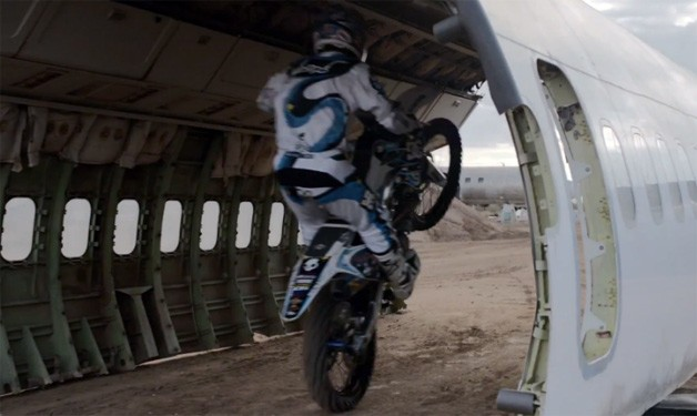 Motorcycle rider Robbie Maddison doing a wheelie inside a plane's carcass - video screencap