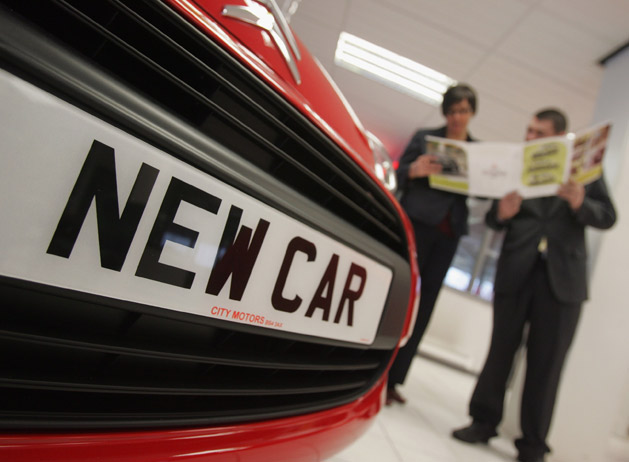 EU car dealership - shoppers with new car