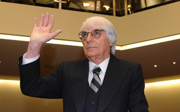 Bernie Ecclestone F1 boss suited with hand up