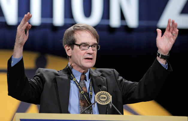 Bob King, UAW boss stands at podium with arms up