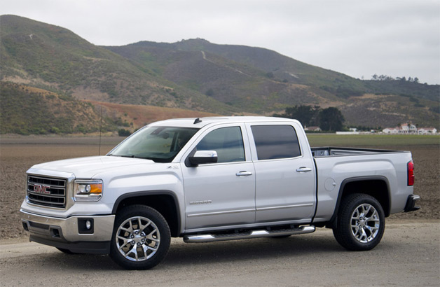 2014 GMC Sierra pickup - silver - front three-quarter view with mountains