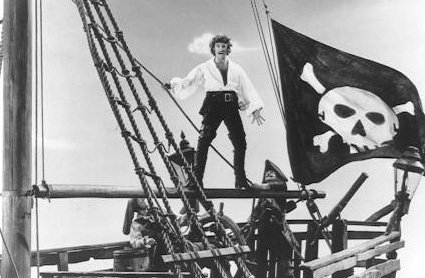 Kevin Kline as the Pirate King stands on a spar just above the stern of his ship, beside the skull and crossbone flag.  His pose is not quite so heroic as above, but the thigh high boots are still looking FINE.