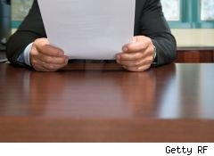 guy looks at a resume over a table