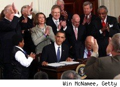 President Barack Obama signs into law health reform legislation that will extend health insurance coverage to millions of uninsured Americans.