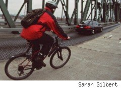 A cyclist commutes to work alongside a car. It's a hard truth that, without our voracious demand for cheap combustible energy, none of this -- the oil spill, the mining disaster -- would have happened.