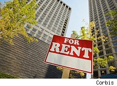 For rent sign in front of highrise