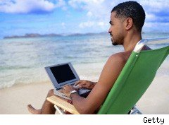 Man uses his laptop on the beach