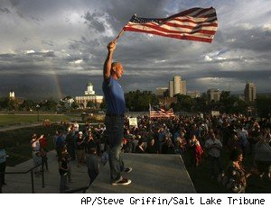 Jeff Key holds the flag above his head as advocates for gay marriage rally on Capitol Hill in Salt Lake City