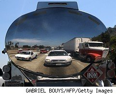 Cars in traffic jam reflected off polished metal of tanker truck
