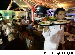 Waiter carries a tray at a restaurant