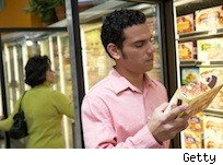 man looks at the label of a frozen food package