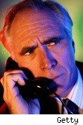 man glowering into telephone