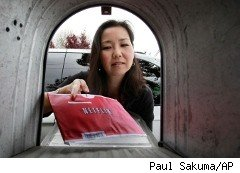 Woman retrieves Netflix envelope from mailbox