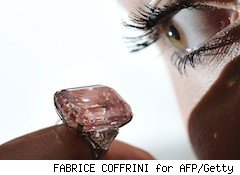 a lady eyeballs a rare pink diamond