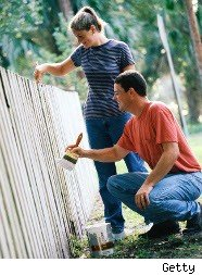 Couple painting a fence