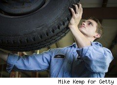 a car mechanic removes a tire