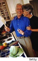 happy retired couple snuggling in the kitchen discussing their Medicare
