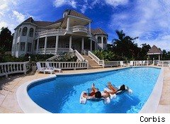 a couple of rich millionaire people in a pool beside a big house