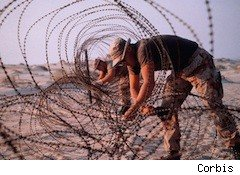 soldier rolling out barbed wire - shipping to military families