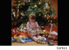 little girl under a christmas tree with present - award winning toys kids special needs