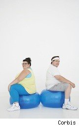 overweight couple sitting - stick to your new year's resolutions