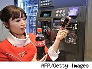 Woman using phone to pay for cola