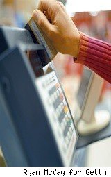a woman swipes a card into a machine - payroll cards