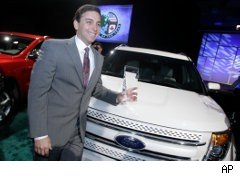 Mark Fields, Ford president of the Americas, stands next to the 2011 Ford Explorer and holds the award for the North American Truck of the Year at the North American International Auto Show in Detroit