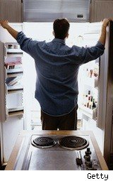 man peers into a fridge - food safety