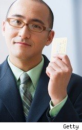 young businessman holding credit card - choosing credit card