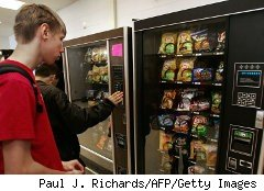 Student searches ofr a snack at a machine