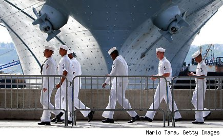 NEW YORK - MAY 22:  U.S. Navy sailors walk past the USS Iwo Jima docked on the Hudson River during Fleet Week May 22, 2009 in New York City. Fleet Week, which annually brings an array of warships to New York City's harbors on Memorial Day weekend, is being celebrated this year with the smallest flotilla of ships since the event began 22 years ago, as budgets have been hampered by the current economic crisis.  (Photo by Mario Tama/Getty Images)
