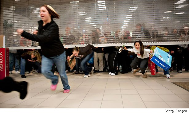 Black Friday shoppers duck under the opening door of a Sears store