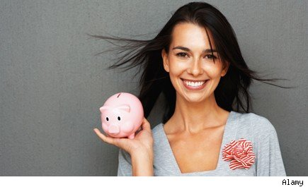 Smiling young woman holding piggy bank