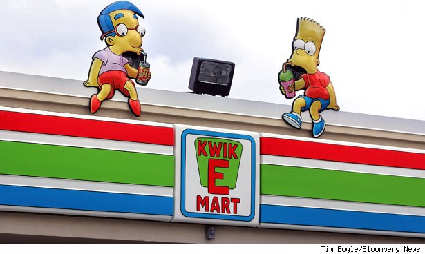 Milhouse Van Houten and Bart Simpson displays sit atop a Simpsons-styled Kwik-E-Mart