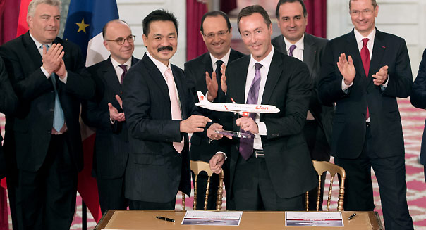 French CEO of European aerospace giant Airbus Fabrice Bregier (C, right) and Lion Air founder and president director Rusdi Kirana (C, left) are applauded by France's President Francois Hollande (C, background), after signing a contract during a ceremony at the Elysee presidential palace in Paris on March 18, 2013. Airbus announced a record order worth 18.4 billion euros ($ 23.8 billion) from Indonesia's Lion Air for 234 medium-haul A320 jets. Lion Air, Indonesia's largest private carrier and one of the world's fastest growing airlines, is a new client for Airbus as it has previously been equipped almost exclusively by US rival Boeing.  AFP PHOTO / BERTRAND LANGLOIS        (Photo credit should read BERTRAND LANGLOIS/AFP/Getty Images)