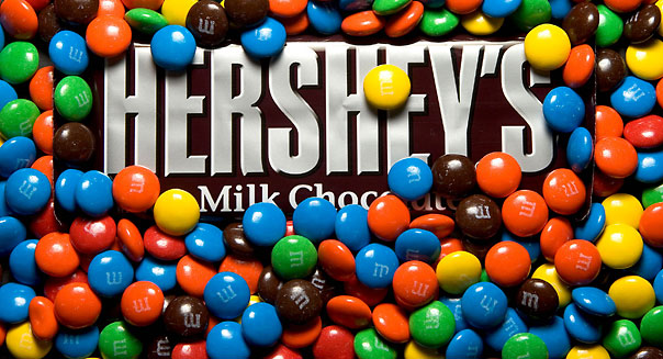 A Hershey's Milk Chocolate Bar is submerged beneath M&Ms, a Mars product, for an illustration in Cambridge, Massachusetts on Wednesday, January 24th. Hershey Co.'s fourth-quarter profit fell 9.9 percent, trailing analysts' estimates, as smaller rival Mars Inc. took a bigger share of the U.S. market.. PHOTOGRAPHER: JB REED