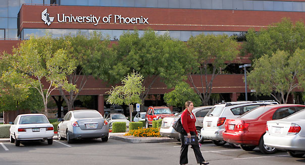 A woman walks through the parking lot of the University of Phoenix, part of Apollo Group Inc., is displayed on a building at their campus in Phoenix, Arizona, U.S., on Wednesday, Oct. 28, 2009. Apollo Group, the biggest publicly traded U.S. educator, plunged the most in 19 months in New York after the company said its accounting is being investigated by the U.S. government. Photographer: Joshua Lott/Bloomberg
