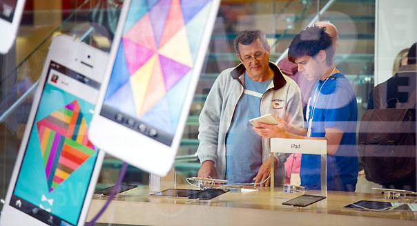 A customer gets help from an employee at an Apple Inc. store in San Francisco, California, U.S., on Friday, April 19, 2013. Apple Inc., is expected to release earnings data on April 23. Photographer: David Paul Morris/Bloomberg