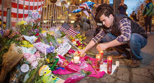 04/16/2013 BOSTON, MA Sam Galvin (cq) 18, of West Roxbury, added candles to a make-shift memorial was set up on the barricades blocking off Boylston Street (cq) at its intersection with Berkeley Street (cq) following yesterday's bombings near the finish line of the Boston Marathon (cq). Galvin's friend is in critical condition following the incident. (Aram Boghosian for The Boston Globe)